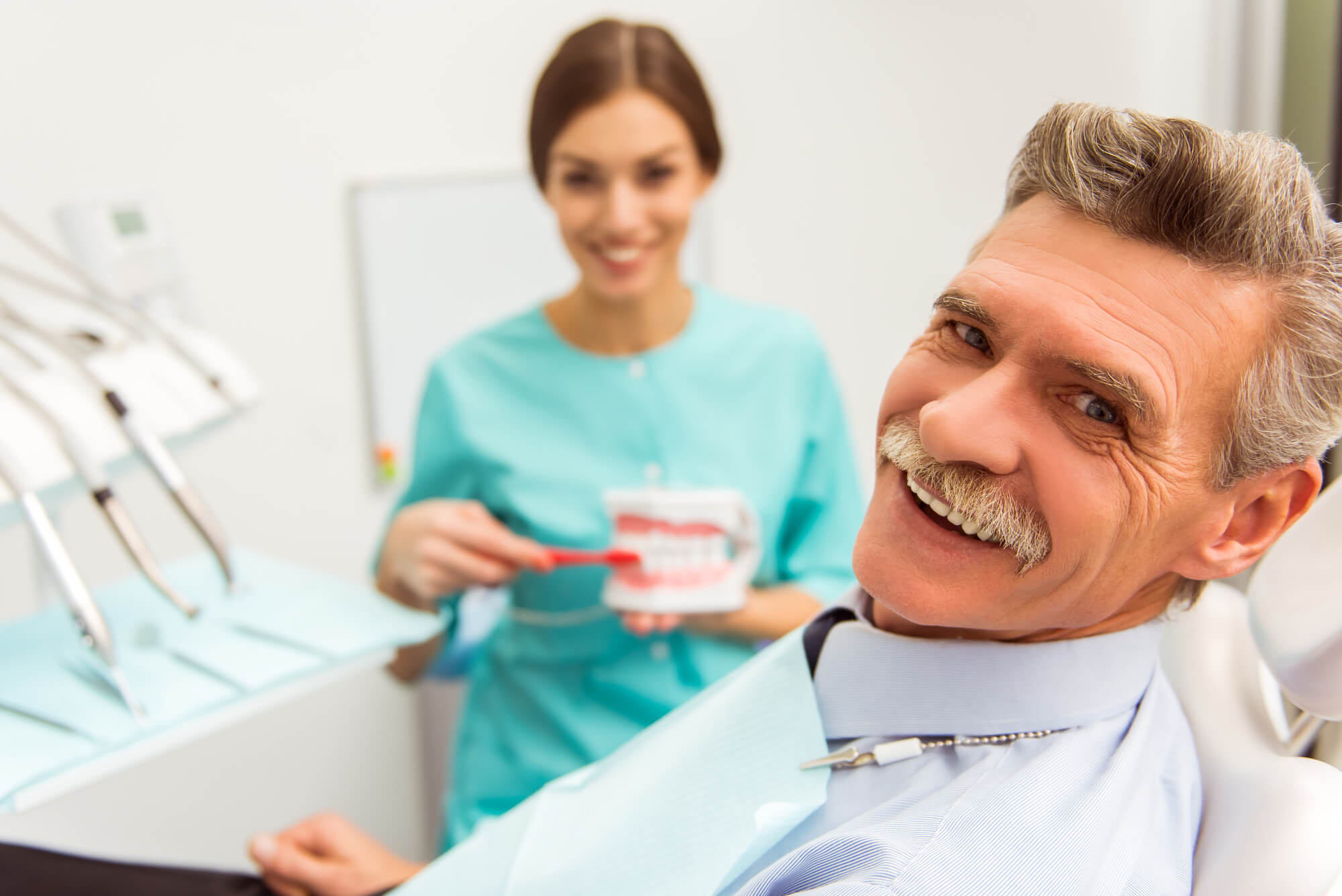 Dentist showing new Teeth in a Day system in plantation to patient