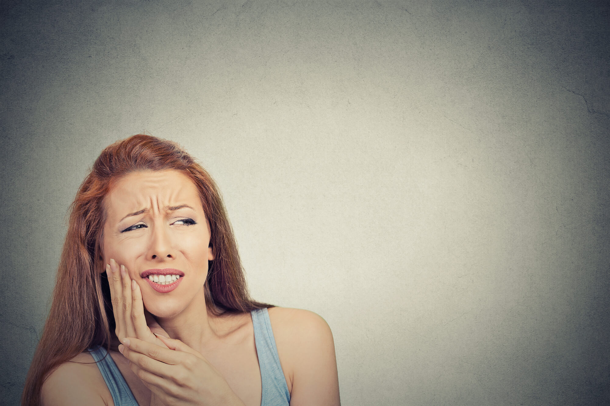 a woman with tooth pain who needs oral surgery in Pembroke Pines FL